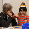 MIKE SPRINGER/Staff photo   <br /> Fara Courtney of Gloucester watches as her four-year-old granddaughter Haley Warren makes her own Christmas ornament at Art Haven prior to the annual lobster trap Christmas tree lighting ceremony Saturday at Police Station Plaza in downtown Gloucester.<br /> 12/09/2017