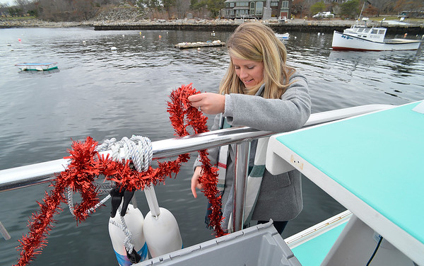 "Leah Drohan helps decorate the Lobster boat ""William G. Drohan""  before it transports Santa to T-Wharf at Rockport Harbor for the annual parade and tree lighting on Saturday December 2, 2017 in Rockport, Ma.  Joseph Prezioso/Photo"