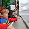 "Kevin, 2, and Gianna Brackett, 4, look out at the shore as they ride along with Santa in the Lobster boat ""William G. Drohan"" on their way to T-Wharf at Rockport Harbor for the annual parade and tree lighting on Saturday December 2, 2017 in Rockport, Ma.  Joseph Prezioso/Photo"