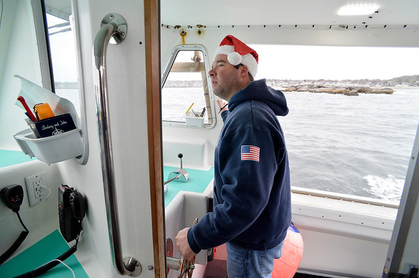 "Captain Ryan Drohan steers his Lobster boat ""William G. Drohan"" around Rockport harbor before transporting Santa and friends to T-Wharf at Rockport Harbor for the annual parade and tree lighting on Saturday December 2, 2017 in Rockport, Ma.  Joseph Prezioso/Photo"