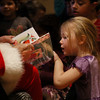 MIKE SPRINGER/Staff photo<br /> Four-year-old Abigail Blosser takes a peek at Santa's book during a special holiday storytime and sing-along Tuesday at the T.O.H.P. Burnham Library in Essex.<br /> 171219