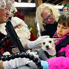 Santa and Mrs. Clause greet Millie Swanson, 10, with her dog Charlotte and mom Barbara in the Old Firehouse on Pleasant St. where the Clauses greeted children after arriving via lobster boat at the T-Wharf at Rockport Harbor for the annual parade and tree lighting on Saturday December 2, 2017 in Rockport, Ma.  Joseph Prezioso/Photo