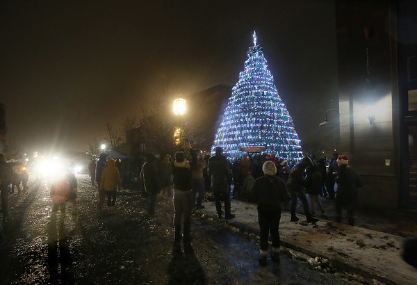 MIKE SPRINGER/Staff photo   <br /> People gather around the lobster trap Christmas tree shortly after the lights were switched on during a ceremony Saturday at Police Station Plaza in downtown Gloucester.<br /> 12/09/2017
