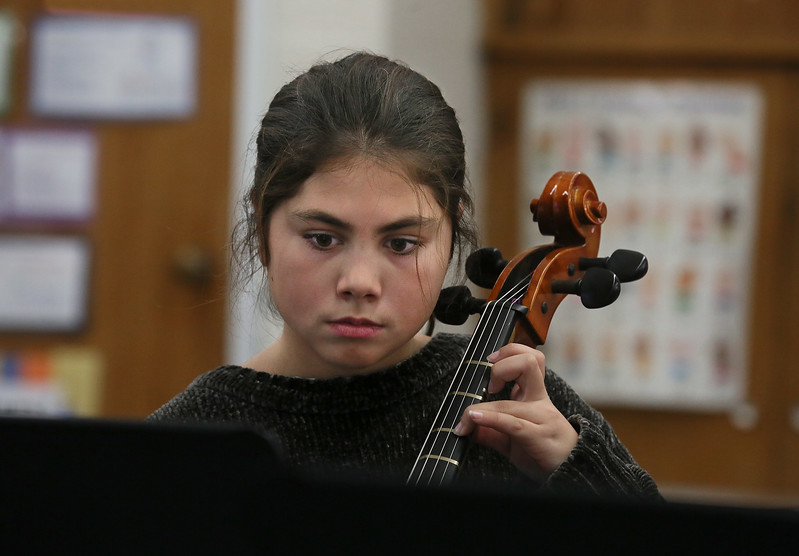 MIKE SPRINGER/Staff photo<br /> Fourth-grader Raquel Rosario practices playing the cello in an after-school strings class at Manchester Memorial School. The class is sponsored by the Manchester Parks and Recreation Department.<br /> 11/28/2017
