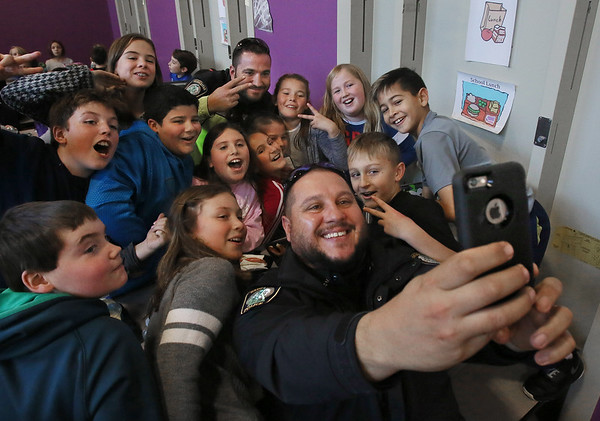 MIKE SPRINGER/Staff photo<br /> Fifth graders gather around Gloucester police officer Joe Parady for a photograph Tuesday during a lunchtime visit  by police to students at Plum Cove Elementary School in Gloucester. In the back is patrolman Peter Sutera.<br /> 12/07/2017