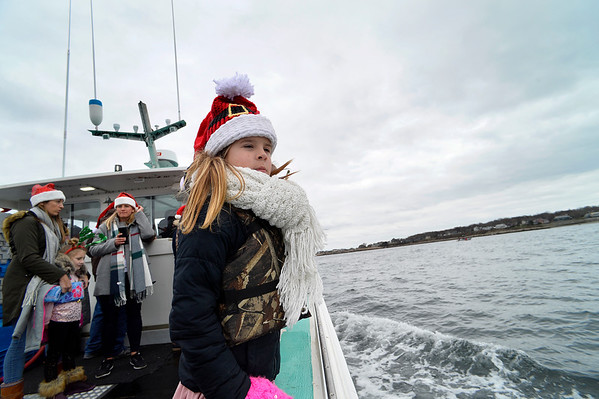 "Lilly Barry, 9, looks out at the shore as she rides along with Santa on the Lobster boat ""William G. Drohan"" where she hitched a ride with her family to help transport Santa to T-Wharf at Rockport Harbor for the annual parade and tree lighting on Saturday December 2, 2017 in Rockport, Ma.  Joseph Prezioso/Photo"