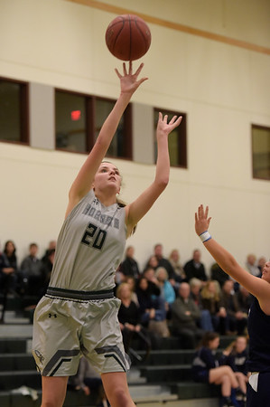 TIM JEAN/Staff photo  Manchester Essex's Emily Jacobsen shoots over Swampscott's Swampscott's Katie Watts during a girls basketball game at Manchester Essex High School.   12/11/18