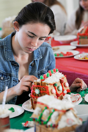 TIM JEAN/Staff photo  Sophia Pomeroy, 17, puts the finishing touch as she decorates a Gingerbread house at the Manchester Community Center.  12/5/18