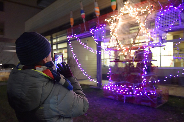 TIM JEAN/Staff photo<br /> <br /> Alex Garasso, 9, of Beverly, snaps a photo og the purple lights that glow on the Lobsta Trap Menorah outside the Temple Ahavat Achim Tuesday night.     12/4/18