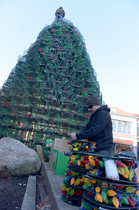 TIM JEAN/Staff photo  Paul Wagner, right, opens the reels of new LED colorful lights as Dave Brooks, top, secures the lobster traps on top of the Lobster Trap Christmas tree in downtown Gloucester. The tree will be light on Saturday, with new LED colorful lights.     12/4/18