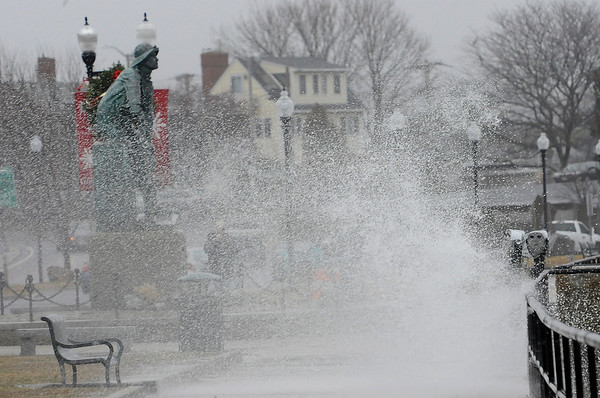 TIM JEAN/Staff photo<br /> <br /> Water sprays up the sea wall and on to the sidewalk near the Gloucester Fisherman's Memorial on Western Avenue.   12/21/18