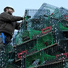 TIM JEAN/Staff photo<br /> <br /> Dave Brooks of Gloucester, secures the lobster traps on top of the Lobster Trap Christmas tree in downtown Gloucester. The tree will be light on Saturday, with new LED colorful lights.     12/4/18