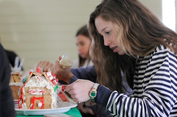 TIM JEAN/Staff photo  Sophie Zalosh, 13, carfully decorates a Gingerbread houses at the Manchester Community Center.  12/5/18