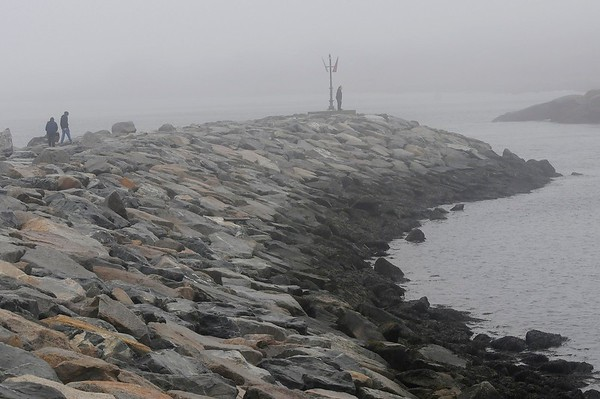 TIM JEAN/Staff photo  People climb on the rocks out towards the point as the fog rolls in along Bearskin Neck in Rockport  12/21/18 [[MER1812211611540653]]