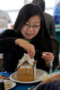 TIM JEAN/Staff photo  Faye Dingle, 15, decorates a Gingerbread house at the Manchester Community Center.  12/5/18