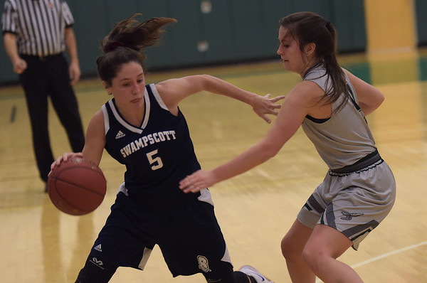 TIM JEAN/Staff photo  Swampscott's Sophia DiGrande, left, drives past Manchester Essex's Grace Brennan during a girls basketball game at Manchester Essex High School.   12/11/18
