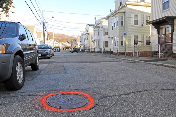 TIM JEAN/Staff photo  A sewer cover is outlined with orange paint on Warner St., in Gloucester. Work is expecteted to begin in the spring on a major sewer project on Trask, Shepherd, Warner, Millett and Sargent Streets. 12/12/18
