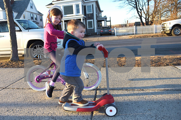 TIM JEAN/Staff photo<br /> <br /> Mackinzie Spence, 8, of Gloucester, and her brother Alexander, 2, ride their bicycle and scooter on the sidewalk of Stacey Boulevard during the unseasonably warm day in February.   2/5/19