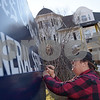 TIM JEAN/Staff photo<br /> <br /> Cheryl Newman-Lahti, owner of Cheryl's Signs based in Gloucester paints new letters on the sign outside of James C. Greely Funeral Services on Washington St., Gloucester.    Cheryl has been painting business signs since 1979 and has also painted hundrends of names on the back of boats in the area.  2/5/19