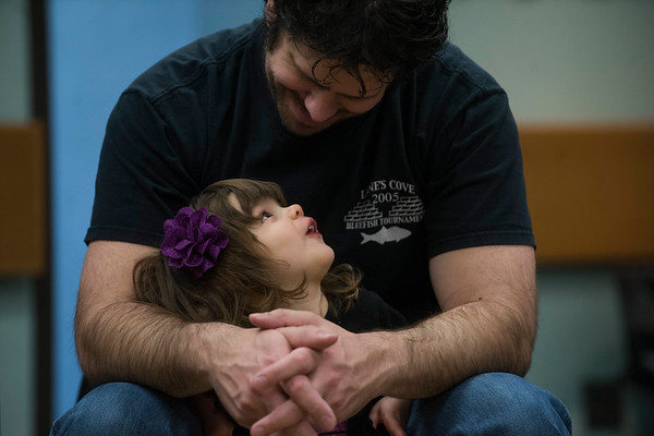 "SAM GORESH/Staff photo. David Robertson talks to his daughter Isabella Robertson, 2, as they listen to local writer Jape Payette reads his ""Jape the Grape Ape from Outer Space"" book to kids during the Dads and Donuts program at the Sawyer Free Library. 2/18/17"