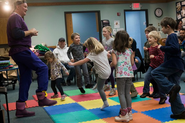 "SAM GORESH/Staff photo. Local writer Jape Payette hops with kids as he reads them his ""Jape the Grape Ape from Outer Space"" book during the Dads and Donuts program at the Sawyer Free Library. 2/18/17"