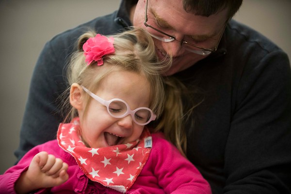 """SAM GORESH/Staff photo. Jeff Magdis and his daughter Samantha Magdis, 3, laugh as they play while listening to local writer Jape Payette reads his """"Jape the Grape Ape from Outer Space"""" book to kids during the Dads and Donuts program at the Sawyer Free Library. 2/18/17"""
