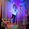 RYAN HUTTON/ Staff photo<br /> Victoria Pool, 5, of Gloucester, manages to balance on one leg while keeping a spinning plate in one hand and a twirling yo-yo in the other during a performance by the Yo-Yo People Rebecca and John Higby at the Rockport Public Library on Tuesday.