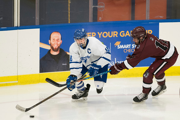 SAM GORESH/Staff photo. Danvers senior Robert Tibbetts prepares to hit the puck as Gloucesterjunior Jack Sperry attempts to stop him on defense in their game at Salem State University. Danvers won the game 4-0. 2/11/17