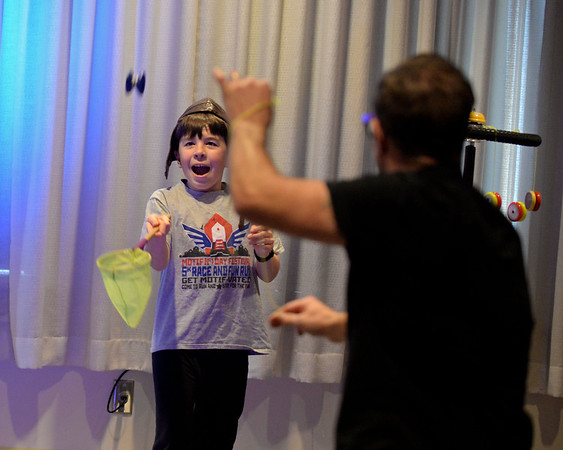 RYAN HUTTON/ Staff photo<br /> Jackson Altieri, 10, tries to catch a flying yo-yo flung by John Higby during a performance by Higby and his wife Rebecca, known as the Yo-Yo People, at the Rockport Public Library on Tuesday.