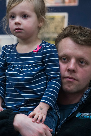 "SAM GORESH/Staff photo. Erik Hinderlie and his daughter Beatrice Hinderlie, 2, listen to local writer Jape Payette reads his ""Jape the Grape Ape from Outer Space"" book to kids during the Dads and Donuts program at the Sawyer Free Library. 2/18/17"