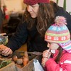 SAM GORESH/Staff photo. Nicole Altieri and her daughter Livia Altieri, 6, look at carrots at the Arrowhead Farm stand at the Rockport Famers Market at Studio Crepe. 2/11/17