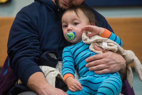 "SAM GORESH/Staff photo. Carlos Pequeno holds his son Magno Pequeno, 1, as they listen to local writer Jape Payette reads his ""Jape the Grape Ape from Outer Space"" book to kids during the Dads and Donuts program at the Sawyer Free Library. 2/18/17"