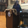 RAY LAMONT/Staff photo<br /> Patricia Huckery of the Massachusetts Division of Fish and Game leads presentation on coyotes with the pelt of a coyote draped over the City Hall podium.