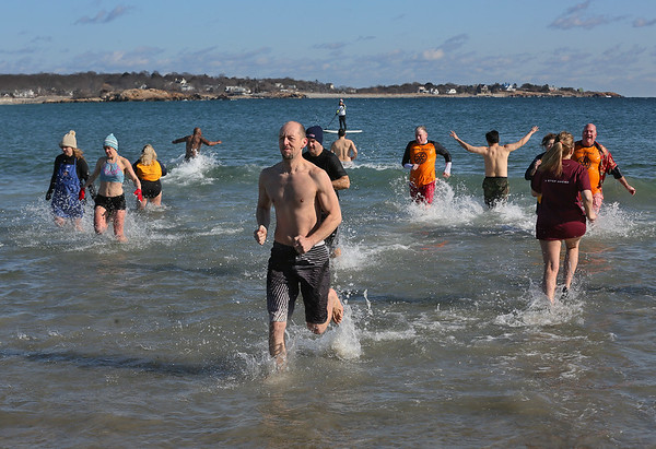 MIKE SPRINGER/Staff photo<br /> Participants run in and out of the frigid water during the Gloucester Rotary Club's 8th annual Polar Plunge on Saturday at Long Beach in Gloucester. The event raised money to fight polio.<br /> 02/03/2018