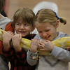 MIKE SPRINGER/Staff photo<br /> Four-year-old Zinnia Souza, left, and Annelise Nicastro, 5, hold a 12-foot snake -- an albino reticulated python -- during a vacation week program Tuesday at the Cape Ann YMCA in Gloucester. Rick Roth and the Cape Ann Vernal Pond Team brought a variety of snakes for the children to look at and learn about. They were allowed to hold several of the snakes.<br /> 2/20/2018