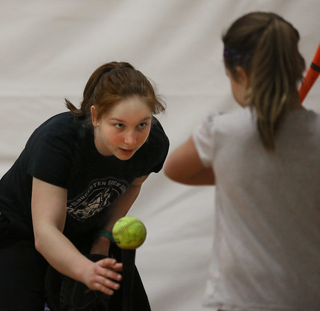 MIKE SPRINGER/Staff photo<br /> Maisie Grow sets up the ball for batter Janelle Brancaleone, 8, during the varsity softball team's vacation softball clinic Thursday at Gloucester High School.<br /> 2/22/2018