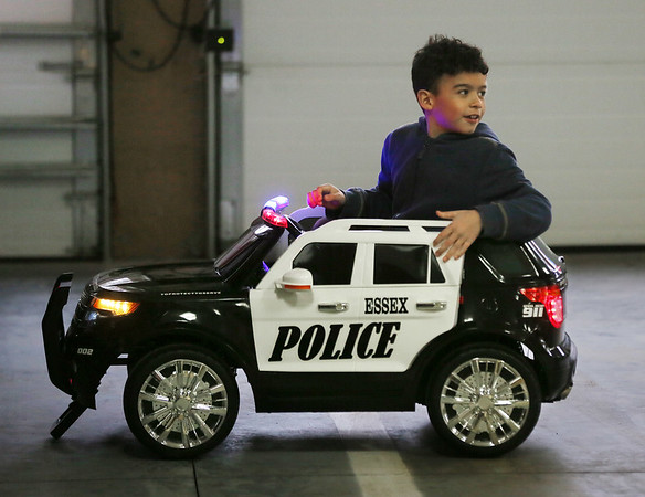MIKE SPRINGER/Staff photo<br /> Seven-year-old Michael Bruce takes his new miniature police cruiser for a ride Thursday after winning the grand-prize drawing at this year's Essex Police Department P.E.T.E. (Police Educational Trading Card Experience) event. Each year Essex police distribute trading cards featuring police officers and staff to children in town. Those who collect the complete set are eligible to win a variety of prizes.<br /> 2/22/2018