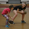 MIKE SPRINGER/Staff photo<br /> Jemima Grow gives fielding pointers to Sage Racofsky, 8, during the varsity softball team's vacation softball clinic Thursday at Gloucester High School.<br /> 2/22/2018