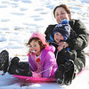 MIKE SPRINGER/Staff photo<br /> Sara Nicastro and her children Noah, 4, and Scarlett, 2, go down the hill together on a sled Monday at Stage Fort Park in Gloucester.<br /> 2/19/2018
