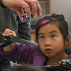 "MIKE SPRINGER/Staff photo<br /> Eight-year-old Lilly Whaley looks at a miniature drone in the hand of John Graham, robotics coordinator with Ocean Alliance, as she turns the propeller of a larger drone during a vacation-week program on whale science at Cape Ann Art Haven in Gloucester.  The children learned about whales and the ""SnotBot"" drones Ocean Alliance uses to study them. Afterwards, they created various art works inspired by what they learned.<br /> 2/20/2018"