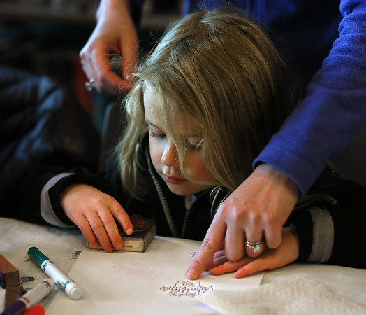 MIKE SPRINGER/Staff photo<br /> Three-year-old Molly McKeen prepares to use a rubber stamp while making a valentine card with the help of her mother, Betsy, during a workshop for children Monday at the T.O.H.P. Burnham Public Library in Essex.<br /> 2/12/2018