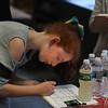 "MIKE SPRINGER/Staff photo<br /> Fifth-grader Miley Courtemanche writes down her answer to a problem during a ""Chemist's Carnival"" Friday at Beeman Elementary School in Gloucester. Students in all three fifth grade classes took part in the event to celebrate the successful completion of a physical science unit on the structure and properties of matter. The children visited a series of stations to watch the making of a number of carnival treats, including popcorn, snow cones, cotton candy, hot dogs and lemonade. They were then tasked with determining whether the food preparation involved a chemical reaction or a simple non-chemical change in the state of the matter making up the food. They had to justify each opinion with a scientific explanation. Along the way, the children enjoyed a modest portion of each treat.<br /> 2/16/2018"