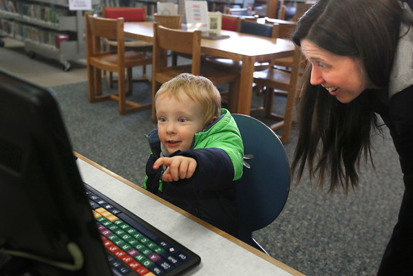 MIKE SPRINGER/Staff photo<br /> Twenty-two-month-old Gabriel Shearer points to something on the computer screen as his mother, Emily, looks on Friday in the children's room of the Sawyer Free Library in Gloucester.<br /> 2/23/2018