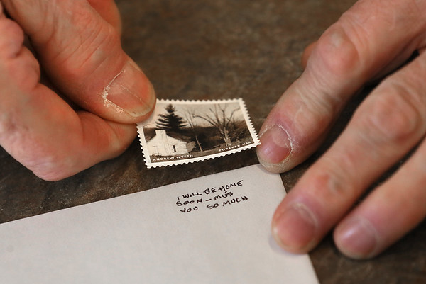 MIKE SPRINGER/Staff photo<br /> Donald Blaskovich demonstrates how he sent secret messages to his girlfriend, Lulu (now his wife), underneath the postage stamp when he was a young man in the U.S. Air Force in the 1950s.<br /> 1/31/2018
