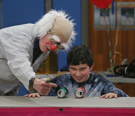 "MIKE SPRINGER/Staff photo<br /> Ted Lawrence of Brattleboro, Vermont, instructs volunteer Sawyer Towne, a fifth grader, how to blow between two aluminum cans to demonstrate Bournoulli's principle during a ""Slapstick Science"" program Tuesday at Veterans Memorial School. Bernoulli's principal states that when the velocity of a fluid, like air, increases, the pressure exerted by that fluid decreases. So, when Sawyer blew air between the two cans, the air pressure between them decreased and the cans rolled together.<br /> 2/13/2018"
