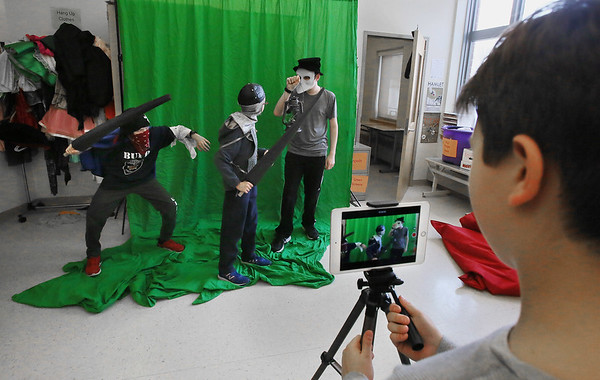 MIKE SPRINGER/Staff photo<br /> Sixth-grader Jan Vytopil, right, uses an iPad to film classmates, from left, Mark Matook, Liam Steele and Gavin Davis in a parody television advertisement at Manchester Essex Regional Middle School in Manchester.<br /> 02/01/2018