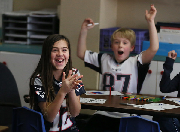 MIKE SPRINGER/Staff photo<br /> Lexi Salah and Jacob Harris cheer at the announcement that their class -- Ruth Flaherty's fourth grade class -- had won the most-spirited door-decorating contest during a New England Patriots Spirit Day on Friday at East Gloucester Elementary School. Students wore Patriots-themed clothing and decorated their classroom doors to show their support for the New England team in this Sunday's Super Bowl game. <br /> 02/02/2018