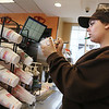 MIKE SPRINGER/Staff photo<br /> Employee Aimee Stuart writes a customer's preferances on a styrofoam cup Friday at the Dunkin' Donuts on Washington Street in Gloucester. The food chain is being forced by a city ordinance to phase out the use of styrofoam sooner than it had planned.<br /> 02/9/2018