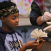 MIKE SPRINGER/Staff photo<br /> Thirteen-year-old Nick Koros folds a sheet of muslin in preparation for dying it during a shibori workshop Tuesday at the Cape Ann Museum in Gloucester. Koros and other members of the Cape Ann YMCA's Teen Leader club spent the afternoon with Kirsten Vega, education coordinator at the museum, learning shibori, an ancient Japanese method of dying cloth with indigo.<br /> 02/06/2018