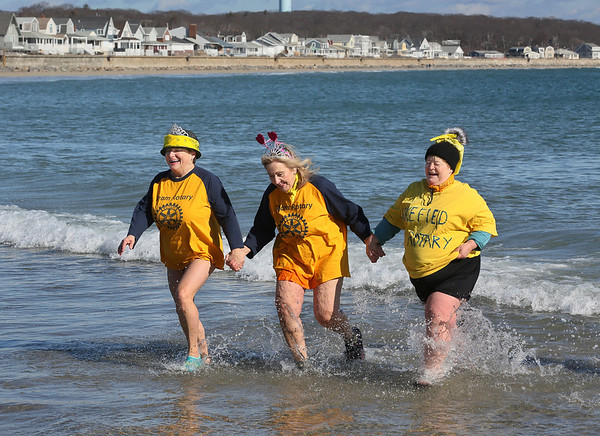 MIKE SPRINGER/Staff photo<br /> From left, Lisa Roderick, Elaine Guaetta and Shelley Finley of the Wakefield Rotary Club come out of the frigid water together during the Gloucester Rotary Club's 8th annual Polar Plunge on Saturday at Long Beach in Gloucester. The event raised money to fight polio.<br /> 02/03/2018